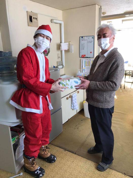 商店街組合へサンタのコスプレでプレゼントする山田院長